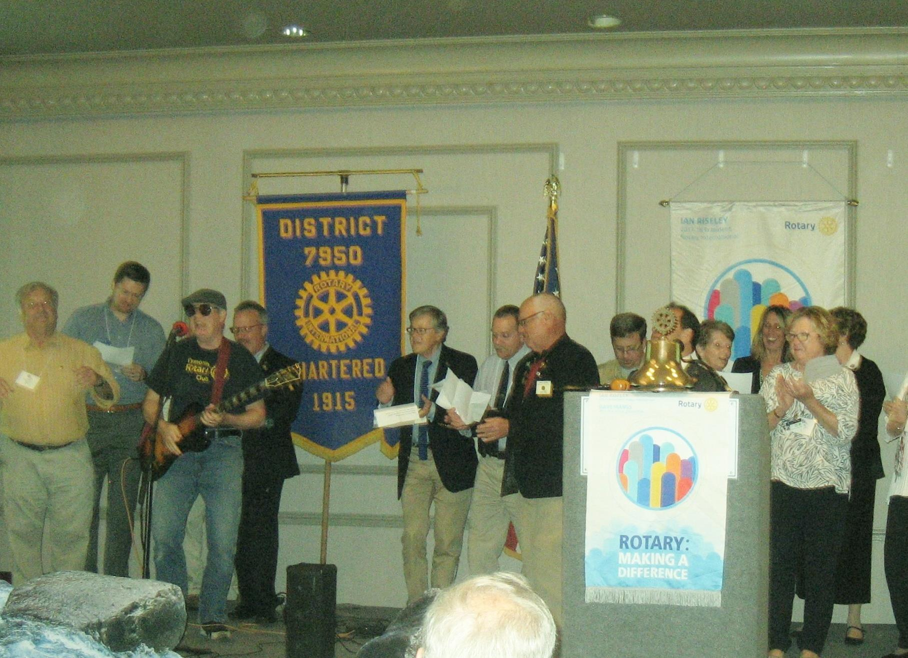 Dennis Carman leads Plymouth Rotarians in the Rotary version of We Will Rock You