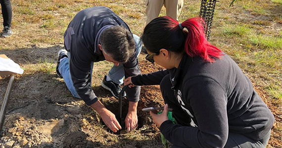 Jessica Connors and Club President Michael Della Rocca plant a tree, an example of the kind of  projects that can give new members ownership and responsibility.