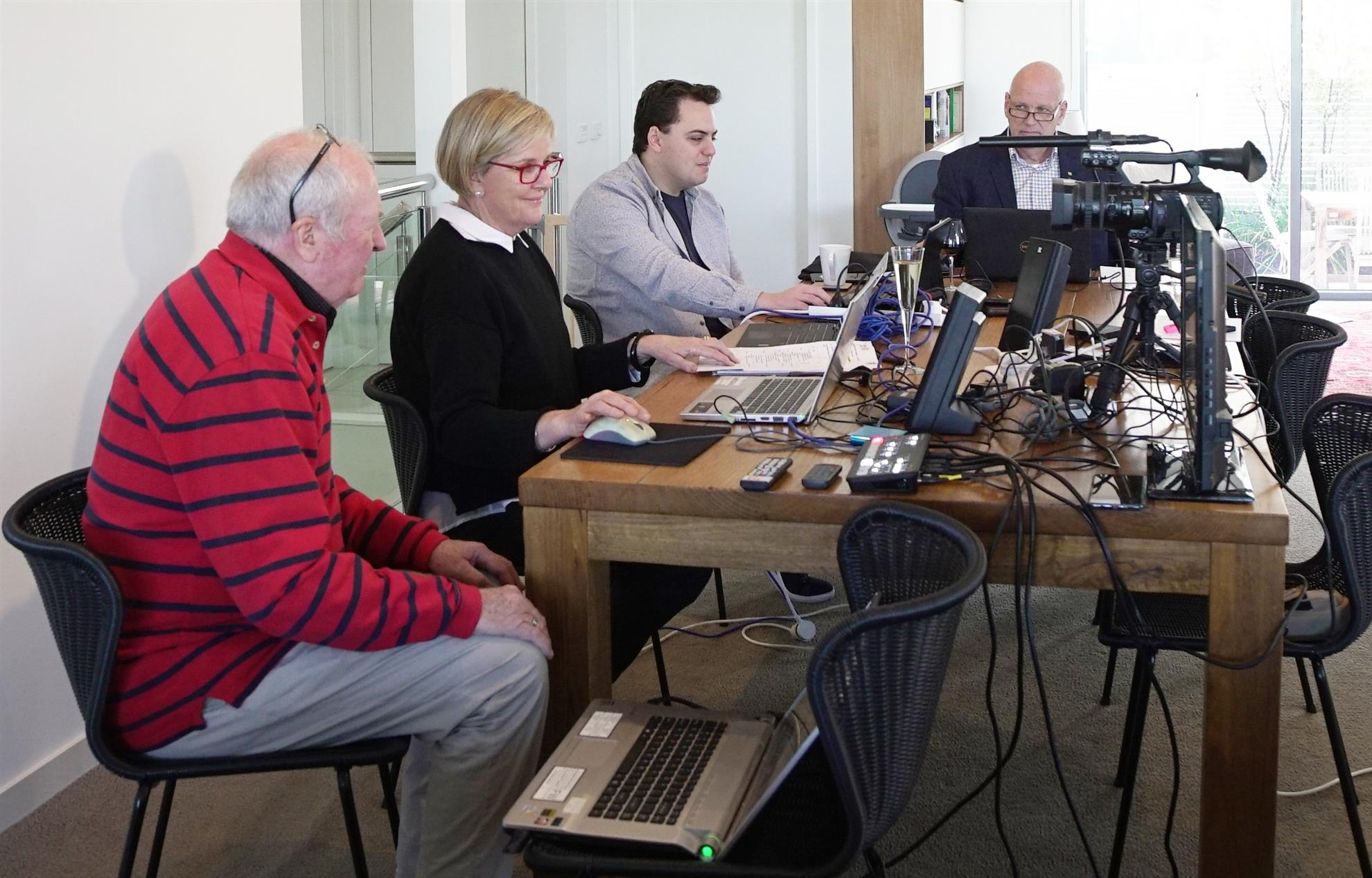 A group of people sitting at a table using a computerDescription automatically generated