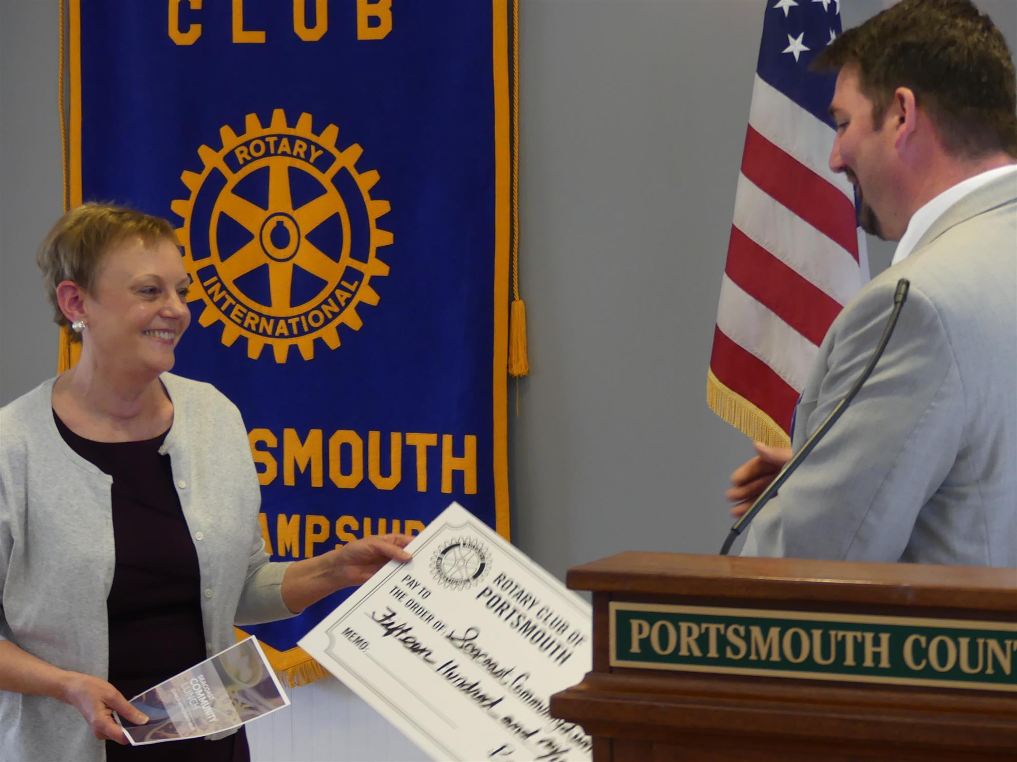 A representative from the Seacoast Community Lunch Program accepts a check  from President Ben Wheeler. 860925e9708