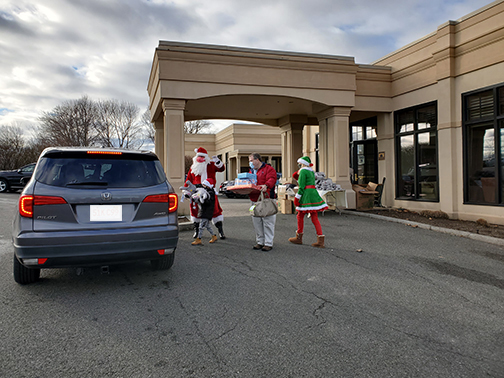 Santa and his elf greet children with gifts.