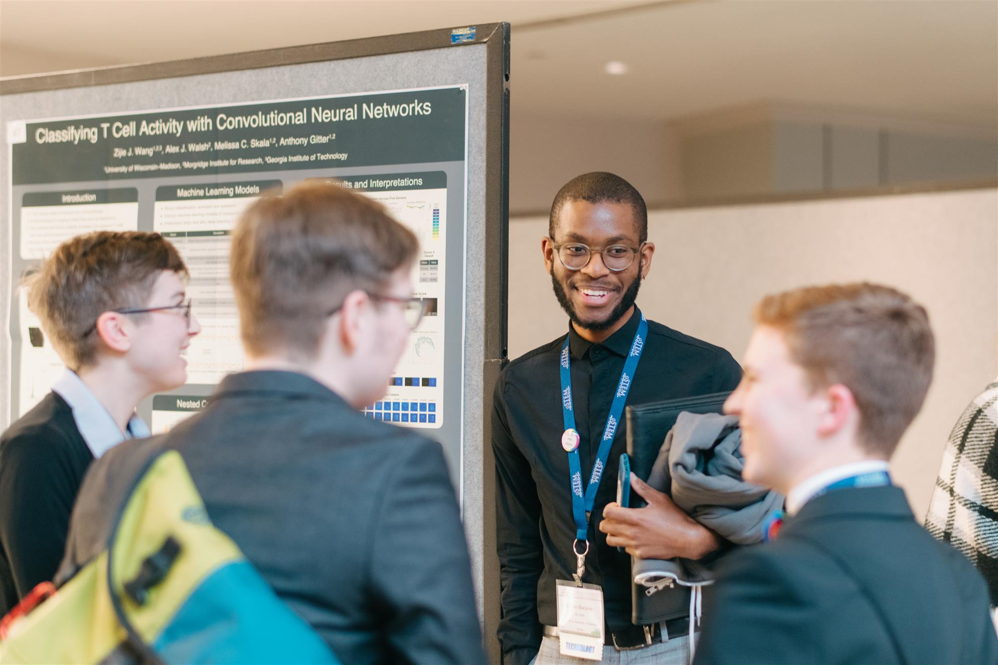 From Conference 2019, Image of people smiling in a conference area and talking
