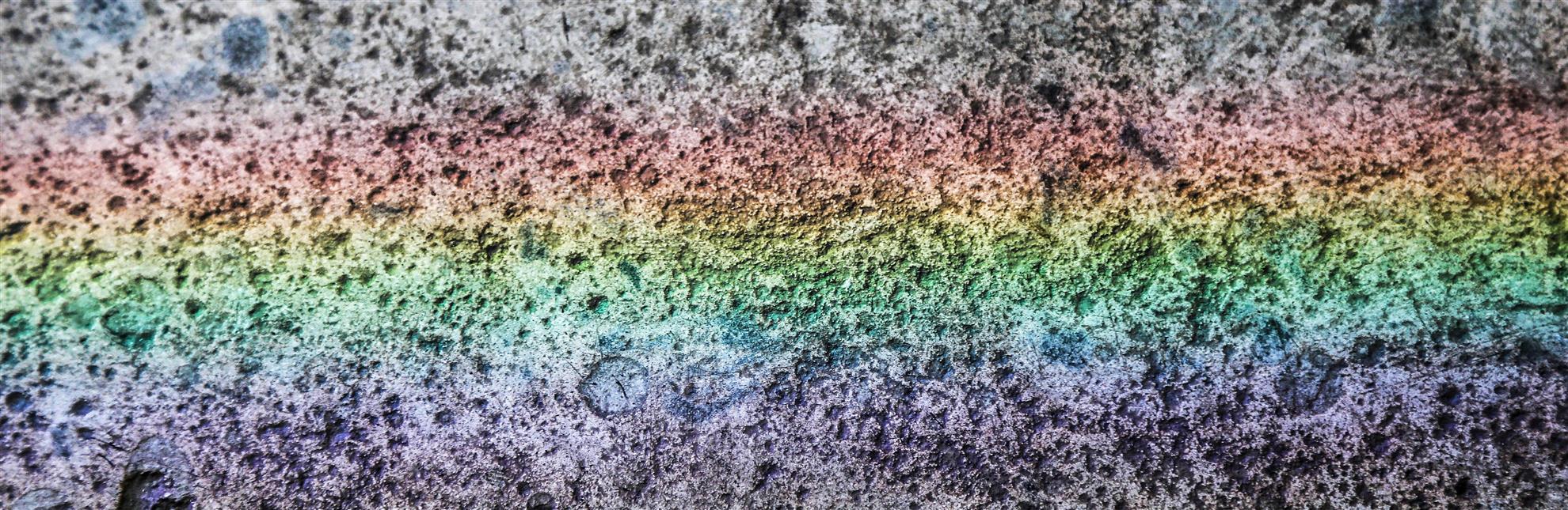 Rainbow light spectrum over darkened concrete.