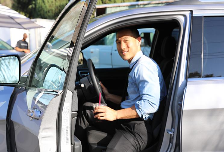 Man smiling while getting out of his car with a cup in his hand.