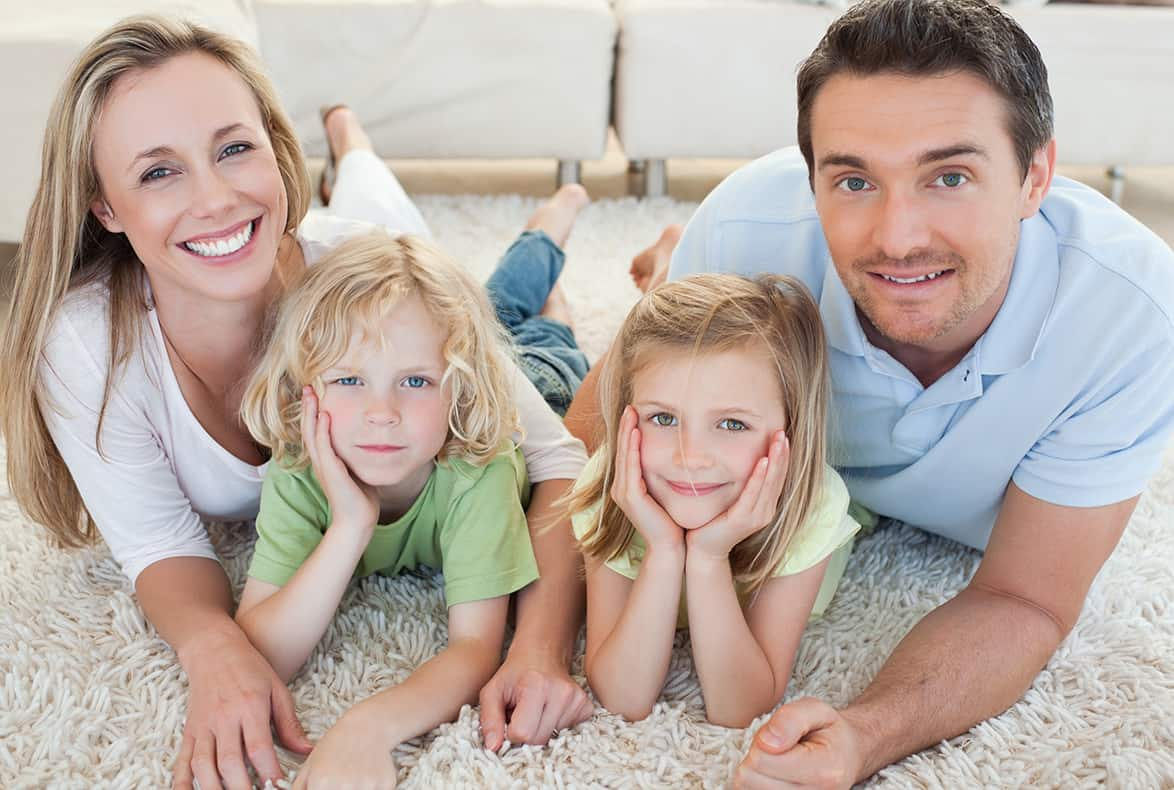 Husband and wife smile with their two children while laying on their white rug in the living room.