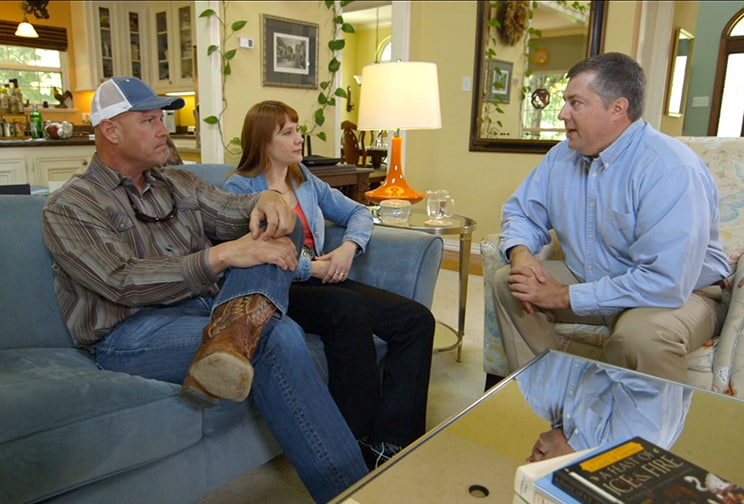 Pipeline instructor and married couple communicate in their living room.