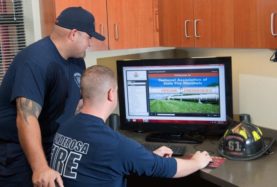 Firefighter assisting another firefighter by walking him through the online training.