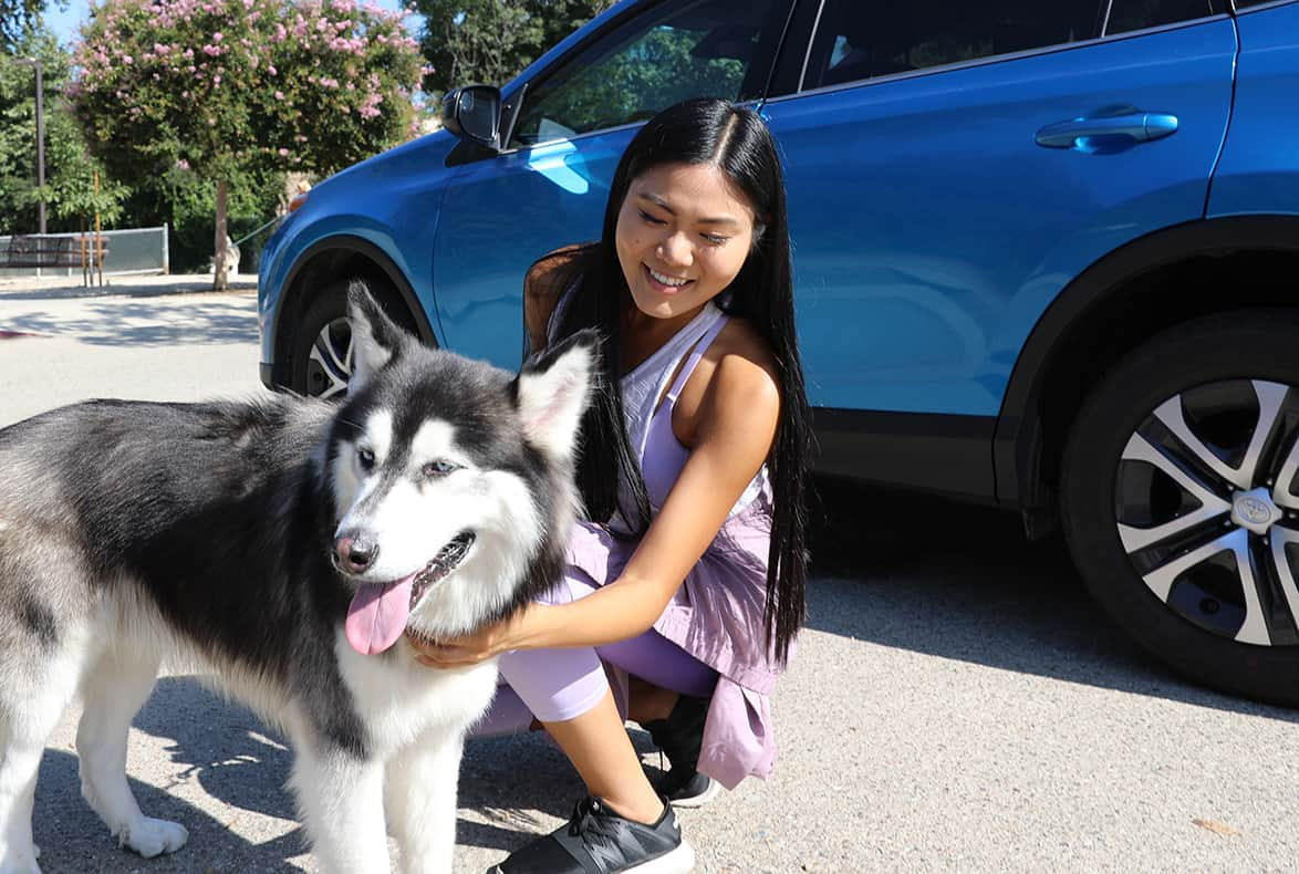 Smiling woman petting her pet husky next to her blue car.