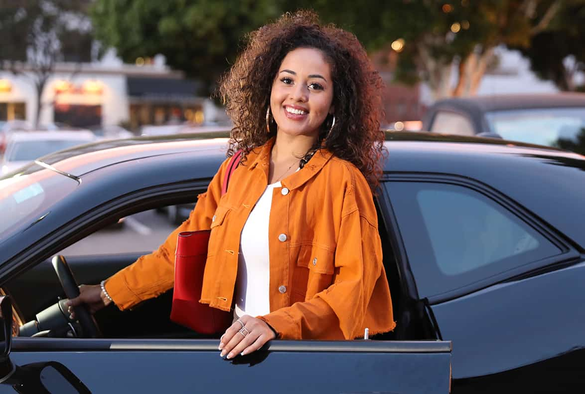 Young woman smiling with her black car