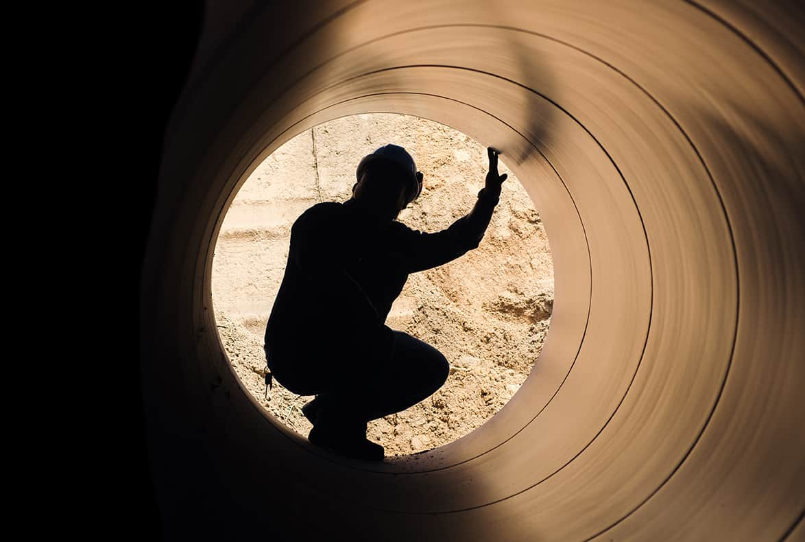 Pipeline worker crouching inside a large pipeline