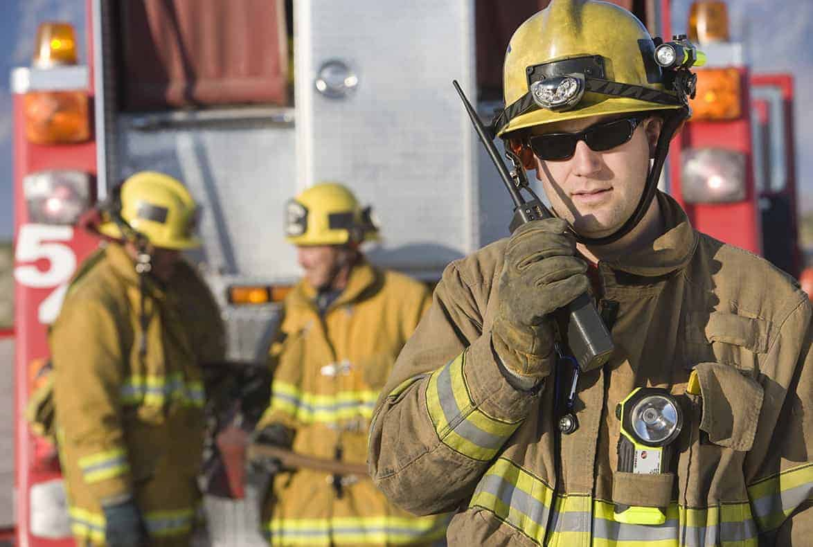 Firefighter talking into his walkie-talkie with firetruck in the background.