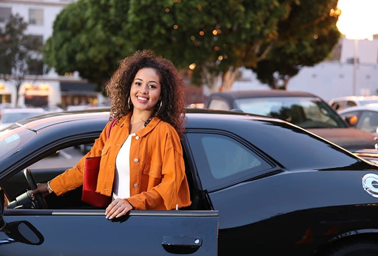 Smiling young woman standing next to her black car